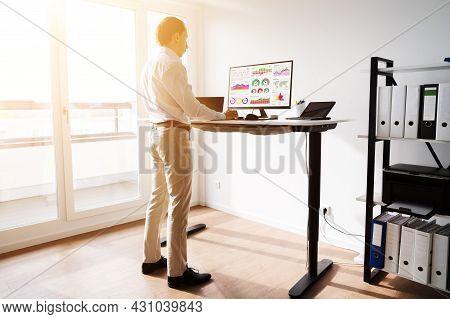 Height Adjusting Stand Desk In Office. Good Posture