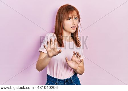 Redhead young woman wearing casual pink t shirt disgusted expression, displeased and fearful doing disgust face because aversion reaction. with hands raised