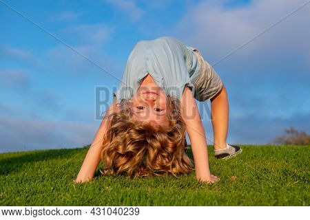 Happy Kid Boy Girl Standing Upside Down On Her Head On Grass In Summer Day. Funny Cute Child Doing F