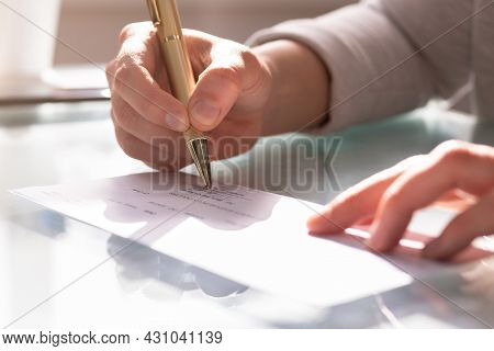 Payroll Compensation Check. Cashier Signing Cheque In Checkbook