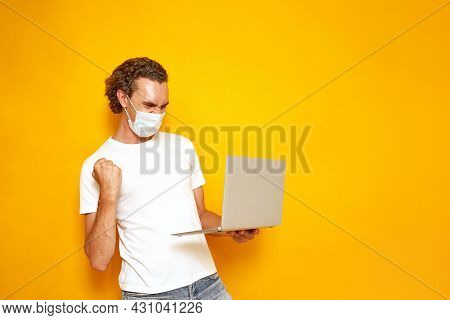 Man In Casual Clothes With Laptop In His Hands And Protective Medical Mask Happy Win Showing Winning