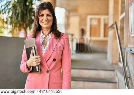 Middle age business woman smilling happy outdoors. Executive holding laptop.
