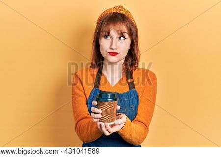 Redhead young woman wearing waitress apron holding take away cup of coffee smiling looking to the side and staring away thinking.
