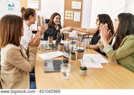 Group of businesswomen smiling and clapping to partners handshake at the office.