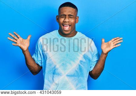 Young black man wearing tye die t shirt celebrating mad and crazy for success with arms raised and closed eyes screaming excited. winner concept
