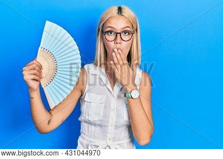 Beautiful blonde woman waving hand fan cooling air in summer covering mouth with hand, shocked and afraid for mistake. surprised expression