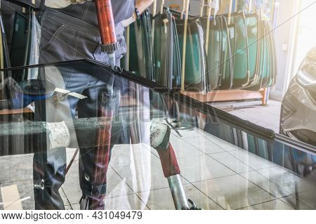 Process Of Preparing Windshield For Replacement In Car Service. Worker Applies Special Adhesive Seal