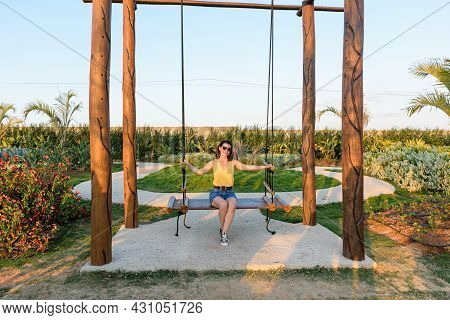 Brazilian Woman, In Sunglasses, Sitting On A Wooden Swing And Enjoying The Sunset.