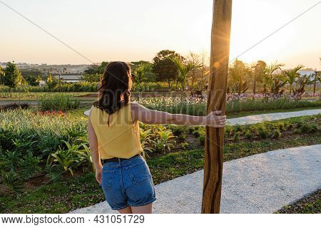Brazilian Woman From The Back Holding A Wooden Pole Admiring The Sunset.