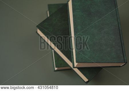 Reading Of Books. Knowledge And Education. Books Stack With Green Covers On A Dark Green Background.