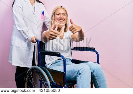 Beautiful blonde woman sitting on wheelchair with collar neck approving doing positive gesture with hand, thumbs up smiling and happy for success. winner gesture.