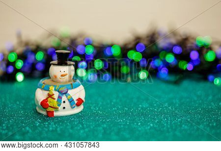 Christmas Lights And Snowman Over Abstract Lights. Merry Christmas And Happy New Year Greeting Card.