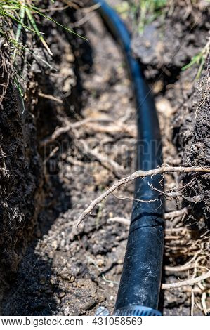 Focus On A Black 1 Inch Sprinkler Plastic Water Line Laid In A Shallow Trench