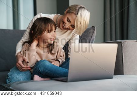 Happy young mother and her little daughter sitting on a couch with laptop computer, looking at screen, on a video call or watching movies