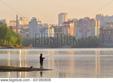 Novosibirsk, Siberia, Russia - 10.05.2019: Fisherman With A Fishing Rod Knee-deep In The Water At Da