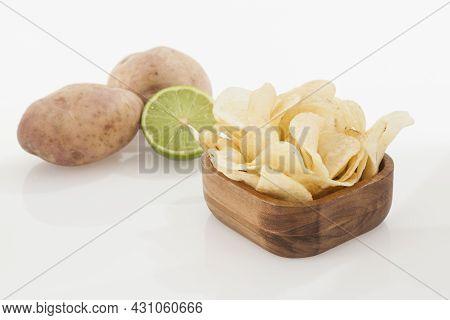 Wooden Bowl With Tasty Potato Chips Lemon Flavor; Photo On White Background