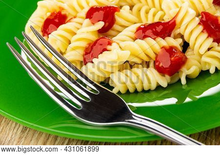 Close Up Of Fork In Green Glass Plate With Boiled Pasta Fusilli With Tomato Ketchup