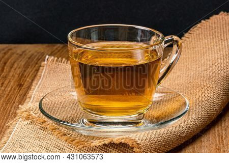 Side View Of A Cup Of Hot Tea In Saucer On Sack Cloth. Hot Tea In A Transparent Glass On Sack Cloth.