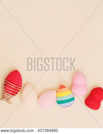 Color Cosmetic Beauty Blender Sponges On Beige Background With Copy Space. Top View Multicolored Sof