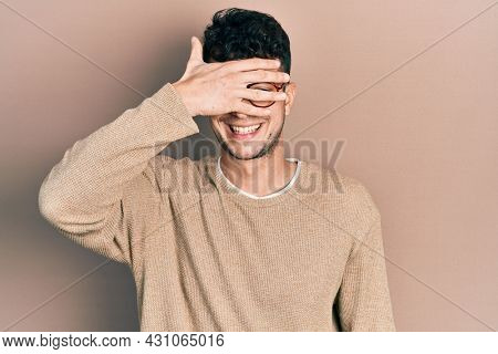 Young hispanic man wearing casual clothes and glasses smiling and laughing with hand on face covering eyes for surprise. blind concept.