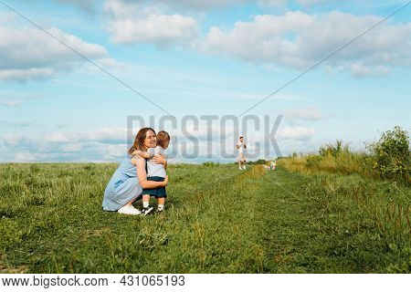 Family Outdoor Recreation. Smiling Young Mother Hugs Small Child In Field, Dad With Dog Is Standing