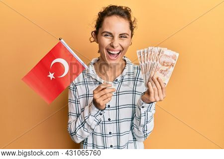Young brunette woman holding turkey flag and liras banknotes smiling and laughing hard out loud because funny crazy joke.