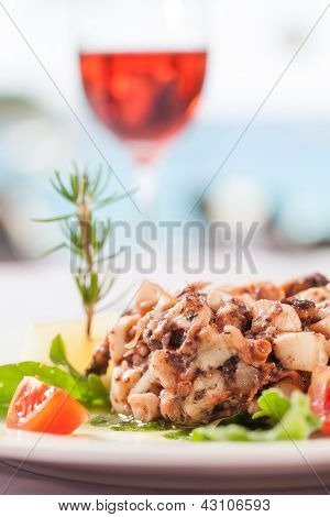 A fish dish served with salad and semi-sweet wine. poster
