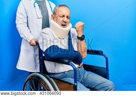 Handsome senior man with beard sitting on wheelchair with neck collar angry and mad raising fist frustrated and furious while shouting with anger. rage and aggressive concept.