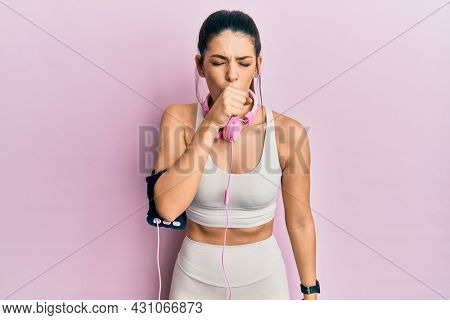 Young hispanic woman wearing gym clothes and using headphones feeling unwell and coughing as symptom for cold or bronchitis. health care concept.