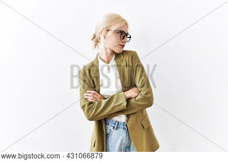Beautiful caucasian business woman standing over isolated background looking to the side with arms crossed convinced and confident