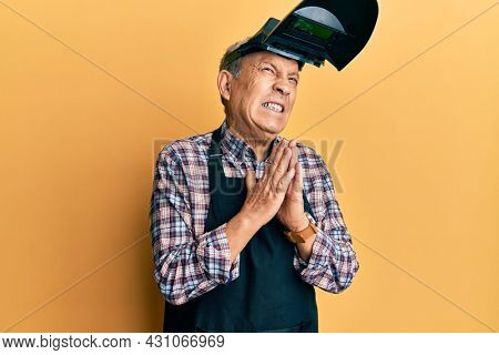 Handsome senior man with grey hair wearing welding protection mask begging and praying with hands together with hope expression on face very emotional and worried. begging.