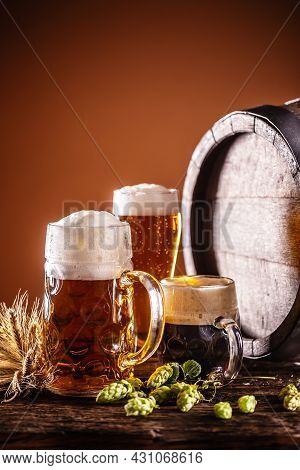 A Liter Glass Full Of Draft Beer Next To It Two Smaller Beers In Front Of A Wooden Barrel As A Decor