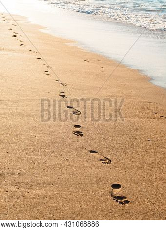 Footprints On The Golden Sand By The Sea In The Evening