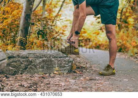 Autumn exercise sport smartwatch runner man tying shoe laces going walking in forest nature park or run on autumn outdoor. Health and fitness active people lifestyle. Yellow leaves foliage.