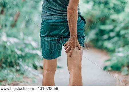 Leg muscle pain sports injury runner man touching painful hamstring muscle. Legs physiotherapy care athlete massaging sore muscles during running training in summer park outside.