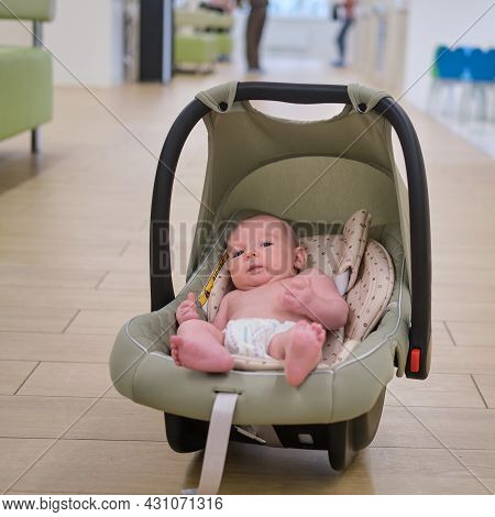 A Child Boy In An Infant Car Seat At A Visit To The Doctor Is Waiting For An Appointment In The Hall