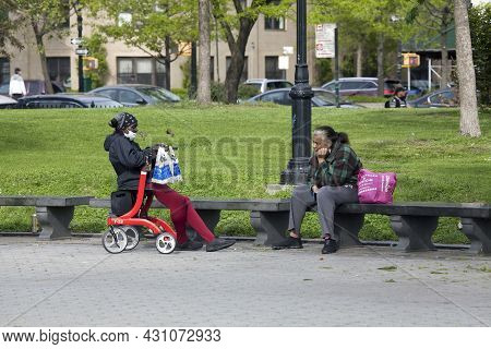 Bronx, New York/usa - May 18, 2020: Two Women Sit In The Park And Talk.
