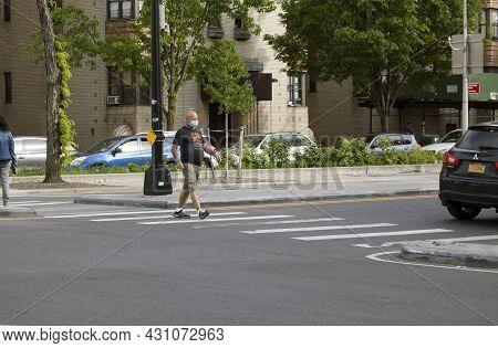 Bronx, New York/usa - May 18, 2020: Man Crossing Street Wearing Face Mask.