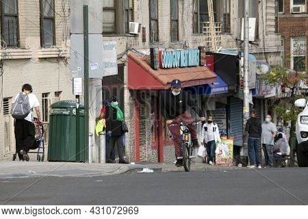 Bronx, New York/usa - March 8, 2020: Young Latino Wearing Mask Rides Bike On Uphill Street.