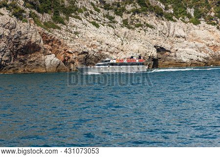 White Ferry Boat With Tourists In Motion In Front Of The Rocky Coast Of The Cinque Terre National Pa