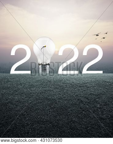 2022 White Text And Light Bulb With Wind Turbine Inside On Green Grass Field Over Aerial View Of Cit