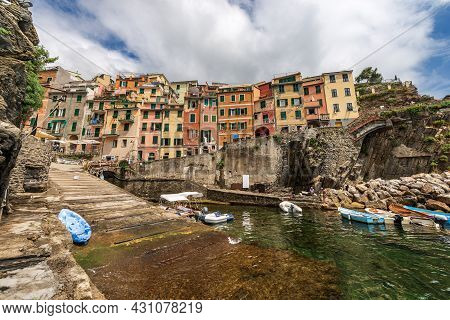 The Famous Riomaggiore Village With Small Boats Moored In The Port, Cinque Terre National Park In Li