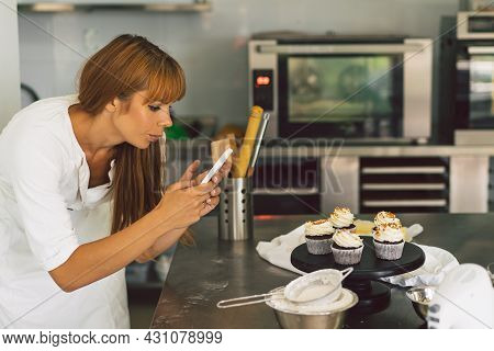Confectioner Girl Photographing Cupcake For Her Blog. Girl Makes A Photo Of Cupcakes On A Smartphone
