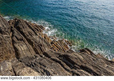 Close-up Of Cliffs And Sea In Front Of The Riomaggiore Village, Cinque Terre National Park In Liguri