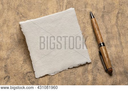 small square sheet of blank white Khadi rag paper with a pen against handmade bark paper