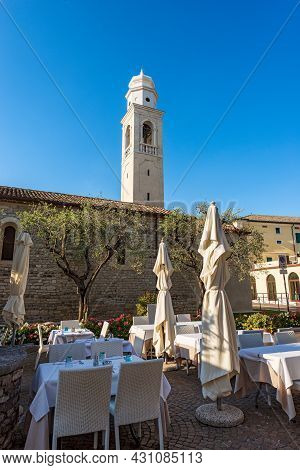Lazise Village. Ancient Church Of San Nicolo In Romanesque Style With The Bell Tower And An Outdoor