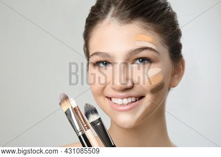Beautiful Girl With Brushes On Light Grey Background. Using Concealer And Foundation For Face Contou