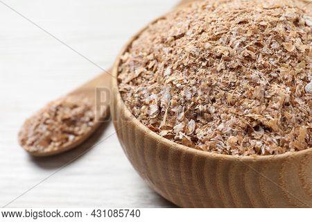 Bowl Of Wheat Bran On White Wooden Table, Closeup