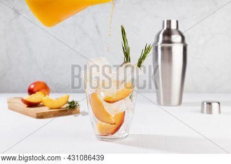 Cooking Healthy Summer Peach Juice - Cocktail Pour Of Jug In Glass With Ice, Rosemary Twig, Sugar Ri