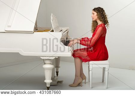 Pretty Blonde Young Woman Playing White Grand Piano. Side View Of Beautiful Elegant Girl Musician We